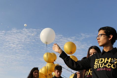 Jovan Guzman, 11, releases a white balloon into the blue sky. A balloon was released for each victim of Saturday