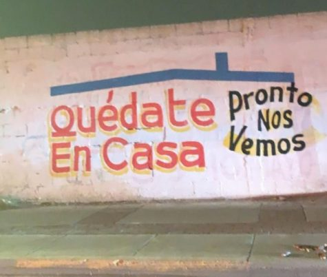 A student takes a photo of a message posted near the border crossing in Ciudad Juarez, to stay at home.